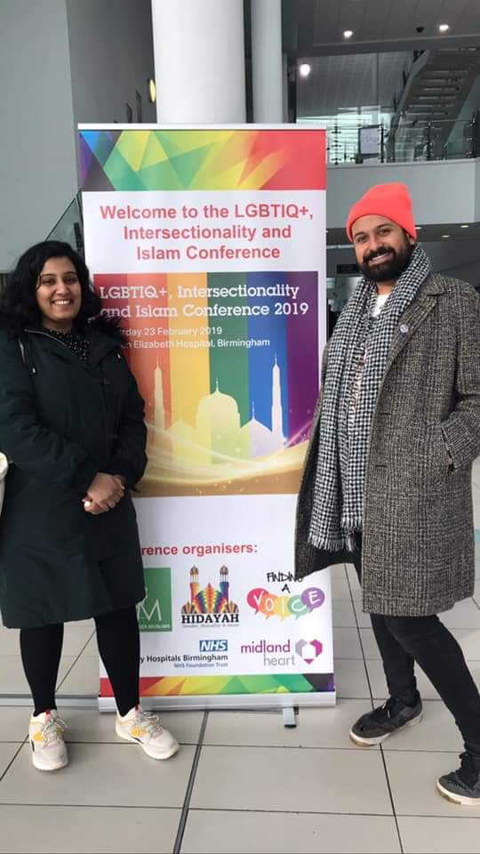 Two smiling people standing in from of LGBT Conference banner